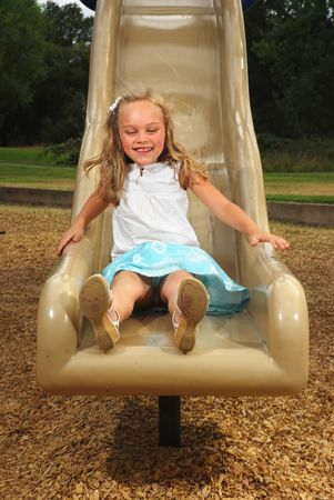 Young girl sliding down a playground slide in summer photo