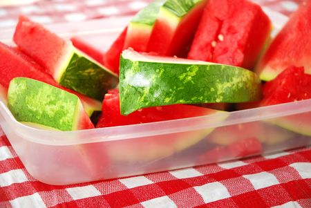 Plastic tub filled with watermelon wedges on picnic table photo