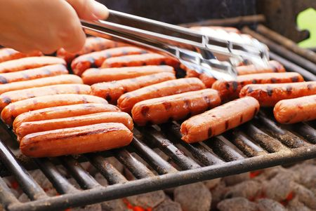 grill:  Rows of hot dogs on barbeque grill at park Stock Photo