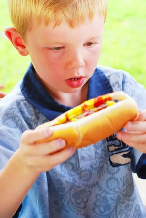 freckled: Young boy excited to eat a big hot dog