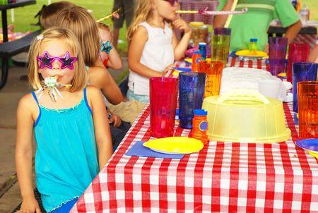 fiesta familiar: Little girl soplando cuerno peri�dico del partido en una fiesta de cumplea�os de Foto de archivo