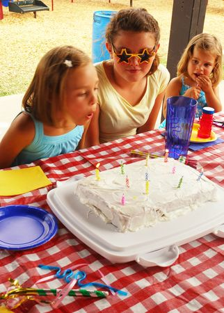 birthday party kids: Young girl blowing out candles on her birthday cake Stock Photo