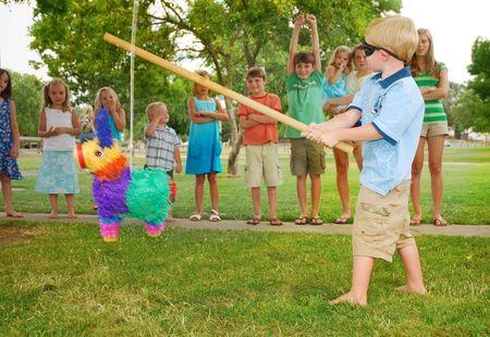 少年は子供の誕生日パーティーでピニャータで棒をスイングします。 写真素材