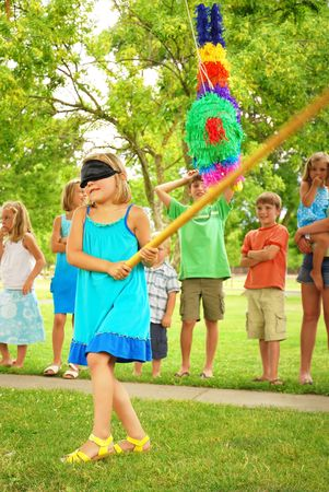 lawn party: Young girl at an outdoor party hitting a pinata