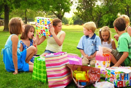 baby open present: Adolescent girl shakes a gift during her birthday party Stock Photo
