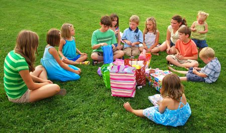 lawn party: Boy opens birthday present with children gathered around