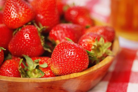 Wooden bowl of fresh strawberries on picnic table photo