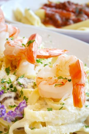 Shrimp atop a plate of Fettuccini Alfredo in restaurant