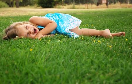 小さな女の子は草の上を敷設しながらあくび
