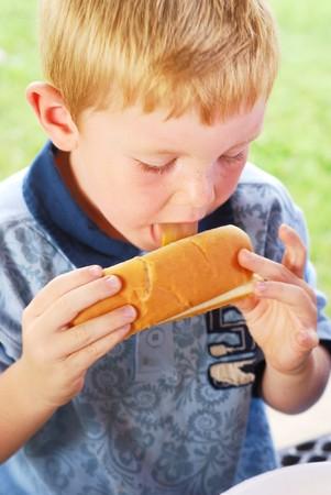 Little boy licking mustard off his hot dog photo