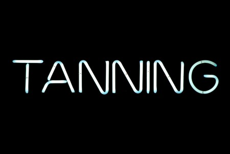 Tanning neon sign isolated on black background 写真素材