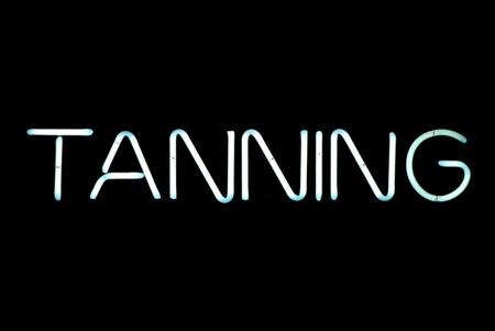 suntan: Tanning neon sign isolated on black background Stock Photo