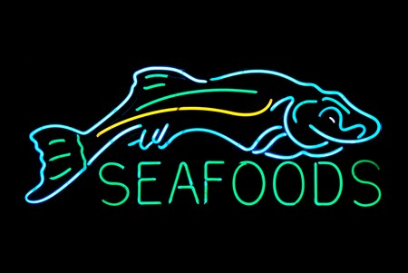 neon fish: Seafood with fish neon sign isolated on black background Stock Photo