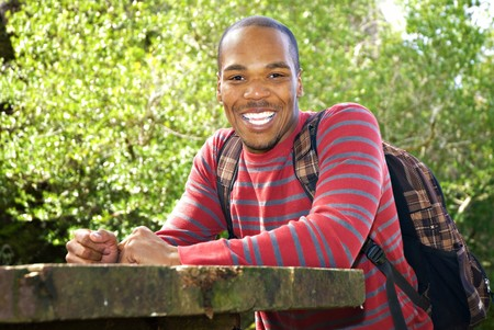 African American student wearing backpack sitting at outdoor table Stock Photo - 7652537