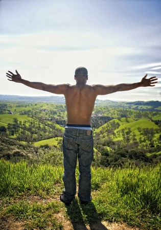 Young African American man standing on hilltop above valley with arms outstretched