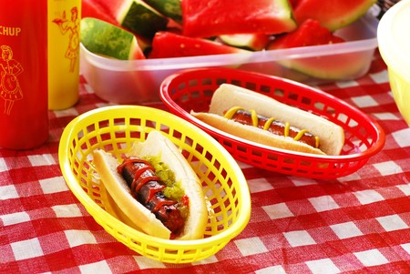 Hot dogs with ketchup and mustard on a picnic table photo