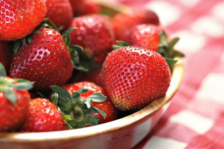 Wooden bowl full of fresh strawberries on a picnic table photo