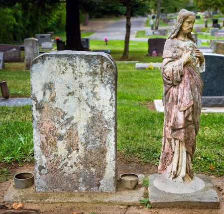 Weathered headstone with blank copyspace next to vintage statue of Jesus Stock Photo