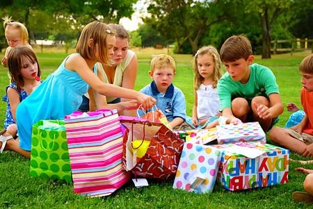 소녀는 그녀의 생일 파티에서 선물을 골라냅니다.