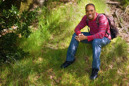 African American college student sitting on a grassy hillside photo