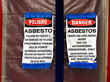 Bilingual asbestos warning signs on plastic covering a front door