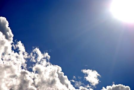 Bright sun and fluffy clouds set against a deep blue sky Banco de Imagens