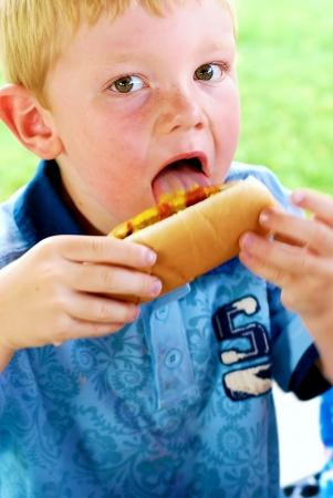 salsa de tomate: Muchacho joven que lame la mostaza y la salsa de tomate al lado de su perro caliente Foto de archivo