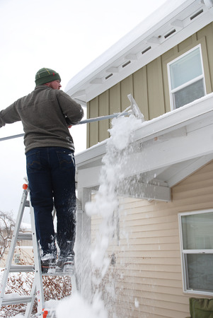 Blanke man met behulp van rake om zware sneeuw schop off dak