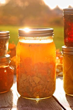 sopa de pollo: Tarro de cristal de la casa en lata de sopa de pollo en el otoño de la luz solar