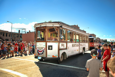 KALISPELL, MONTANA - JULY 4, 2016: Trolley cars from the Montana Trolley Company in Kalispell drive down Main Street during 4th of July Parade.