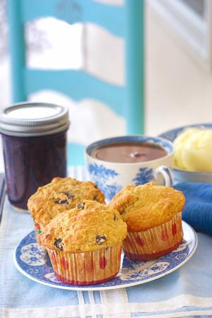 magdalenas: Placa de la vendimia de grano entero (trigo  avena  almendras) muffins de arándanos con mermelada de arándanos, mantequilla fresca, y una taza de té negro caliente Foto de archivo