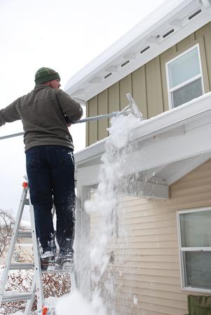 Caucasian man using rake to shovel heavy snow off roof Standard-Bild