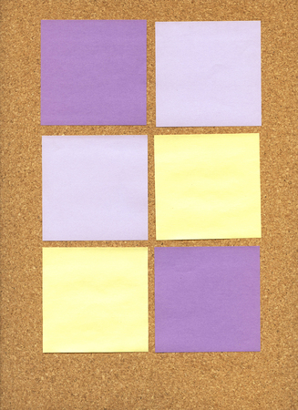 Purple and yellow sticky notes on a corkboard Stock Photo