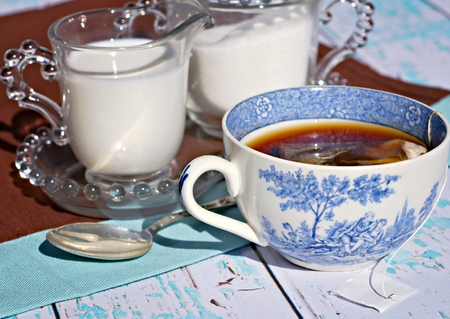 Tea in an antique teacup with milk and cream on rustic table Imagens
