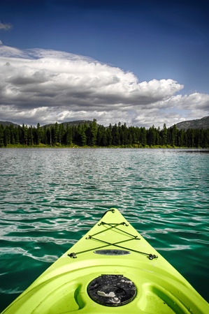 neon green: Neon green kayak on the water at Horseshoe Lake, Montana Stock Photo