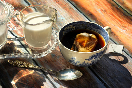 Cup of tea in antique cup with milk and sugar on rustic background