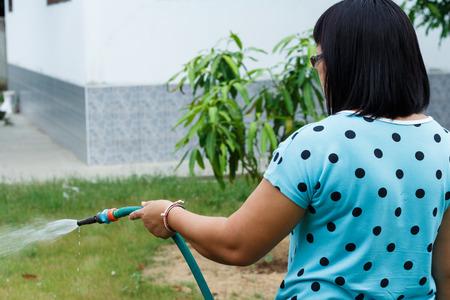 cabello corto: Mujer riego azul negro chaleco de pelo corto en el jard�n de la foto