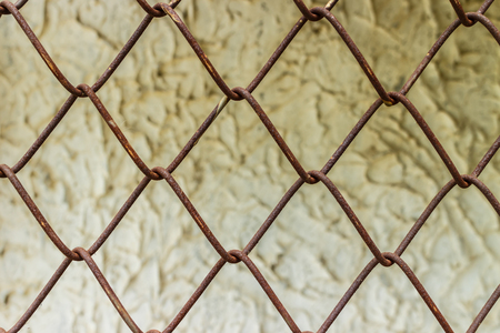 football field: old steel wire chain link net fence photo stock with old factory background Stock Photo