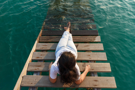 lie forward: Woman lie at wooden stair into the sea and looking forward.