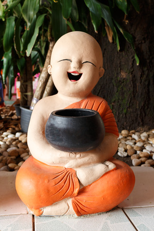 ordain: Statue of Novice Sculpture, Young happy monk sitting Stock Photo