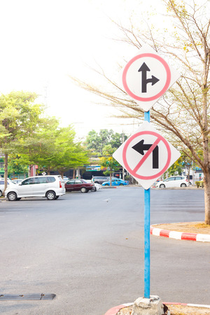 trip hazard sign: signage traffic sign dont turn left and go straight and turn right on blue pole in car park Stock Photo