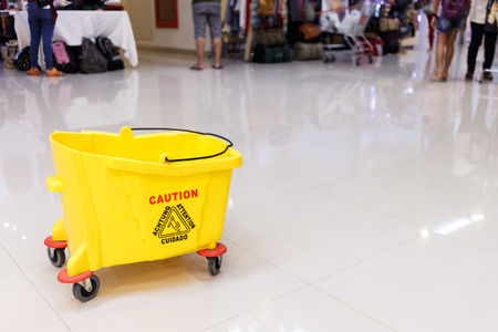 mopped: Mop bucket and caution sign on wet floor at shopping mall