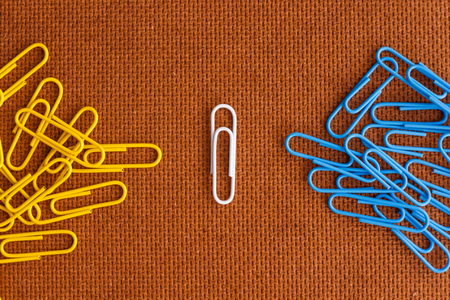 white and blue and yellow paperclip unique concept on wood background Stock Photo