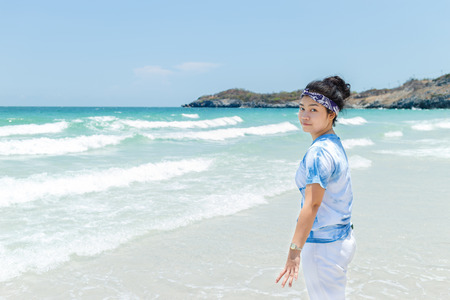 turn back: Young asian woman blue and white shirt stand at beach and turn back Stock Photo