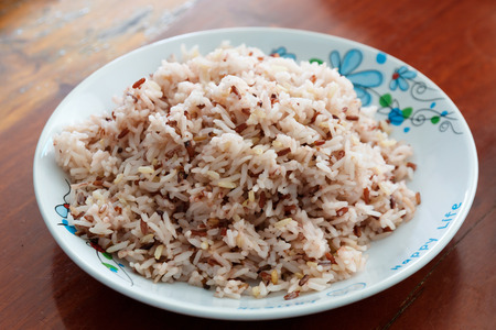 thialand: Brown and white rice mix in white dish on wood table  background