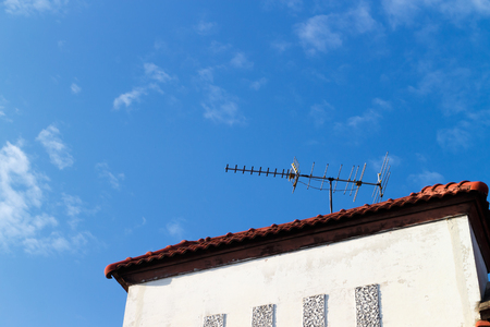 tv antenna: old TV antenna on roof photo,blue sky background