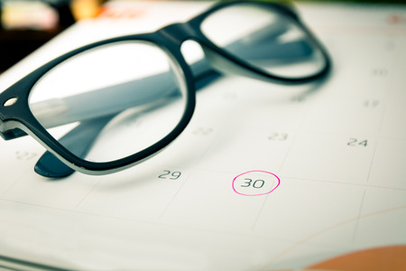 marking up: close up calender and marking with pink circle and eyeglasses, very soft focus and vintage tone