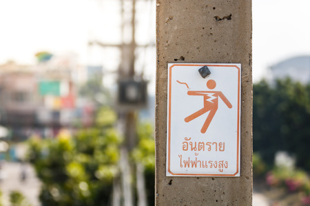 or electrocution: warning label at electric pole, danger is high voltage thai language