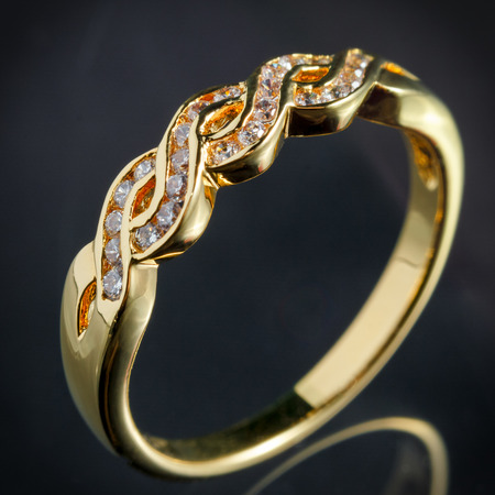 fiancee: close up gold diamond ring on gray background, vignette effect
