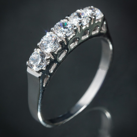 fiancee: close up silver diamond ring on gray background, vignette effect Stock Photo